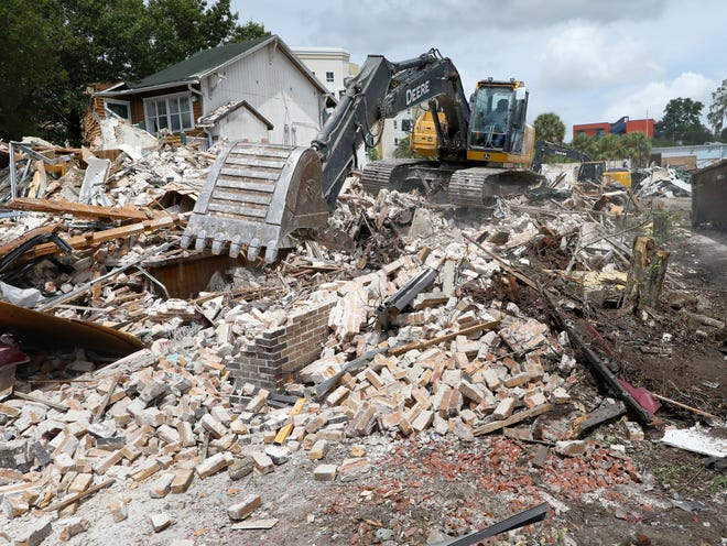 An excavator knocks down walls and picks up rubble from a shopping plaza near The Swamp Restaurant, on Monday in Gainesville. A student housing development with shopping on the ground floor is planned for the location.