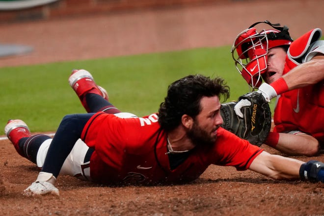 Atlanta Braves' Dansby Swanson, left, dives into home plate and is tagged out by Philadelphia Phillies' Andrew Knapp, right, during the ninth inning of a baseball game on Sunday, Aug. 23, 2020, in Atlanta.