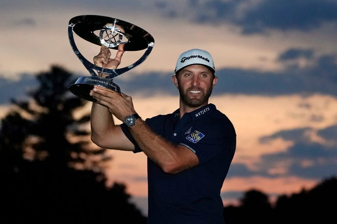 Dustin Johnson holds the trophy after winning the Northern Trust golf tournament at TPC Boston. CHARLES KRUPA/AP