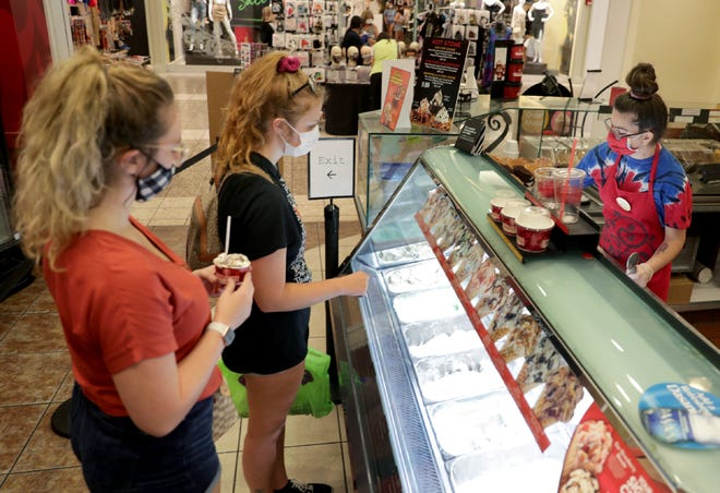 Cold Stone Creamery's assistant manager Liv Lacayo helps customers Sara, left,   and Rebeka Long in the Fox River Mall shop.