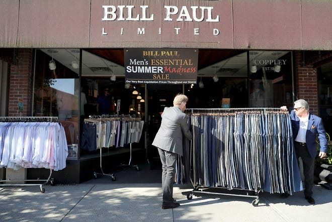Owner Bill Paul, right, and sales associate Guy Wieseler move sale items to the sidewalk in front of the Bill Paul Limited store in Neenah as part of an ongoing summer promotion.