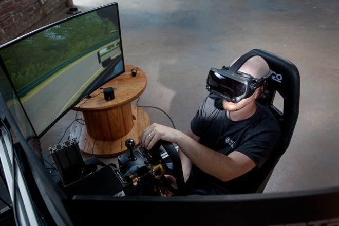 """Joel Bergstein sits behind the wheel of a virtual race car at the Track at Asheville August 22, 2020, in Biltmore Village. """"It's unbelievable how immersive the whole experience is,"""" said Bergstein."""
