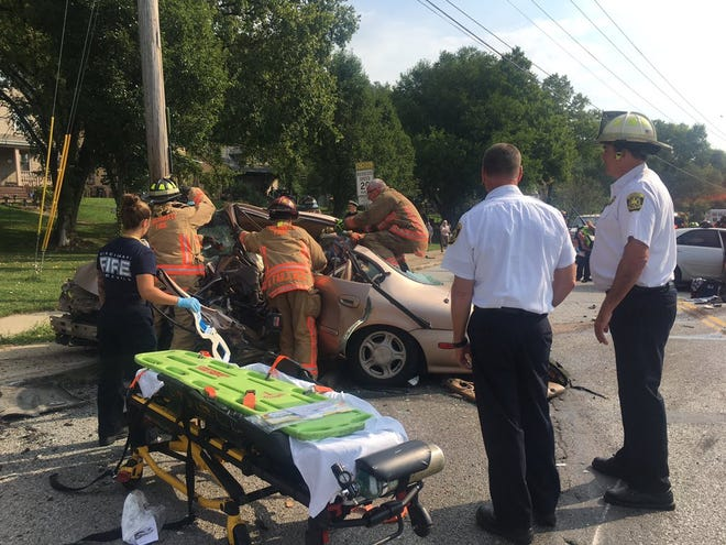 Cincinnati firefighters work to pull a person from a car involved in a two-vehicle crash Monday on River Road at Hillside Avenue on the city's West Side.
