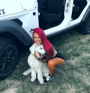 Kristina Williamson hugs her dog Maverick, who was adopted in April 2020 during the coronavirus quarantine. They ride together in her 2020 Jeep Wrangler, named one of the top vehicles for dog owners by Autotrader.com.