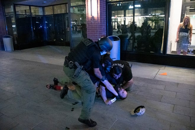 Multiple police officers arrest Detroit resident Kevin Kwart near his apartment lobby in downtown Detroit in the early morning hours on August 23, 2020.