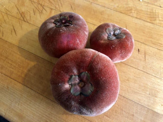 Mabolo fruits are fuzzy like peaches with the tomato shape of a persimmon.