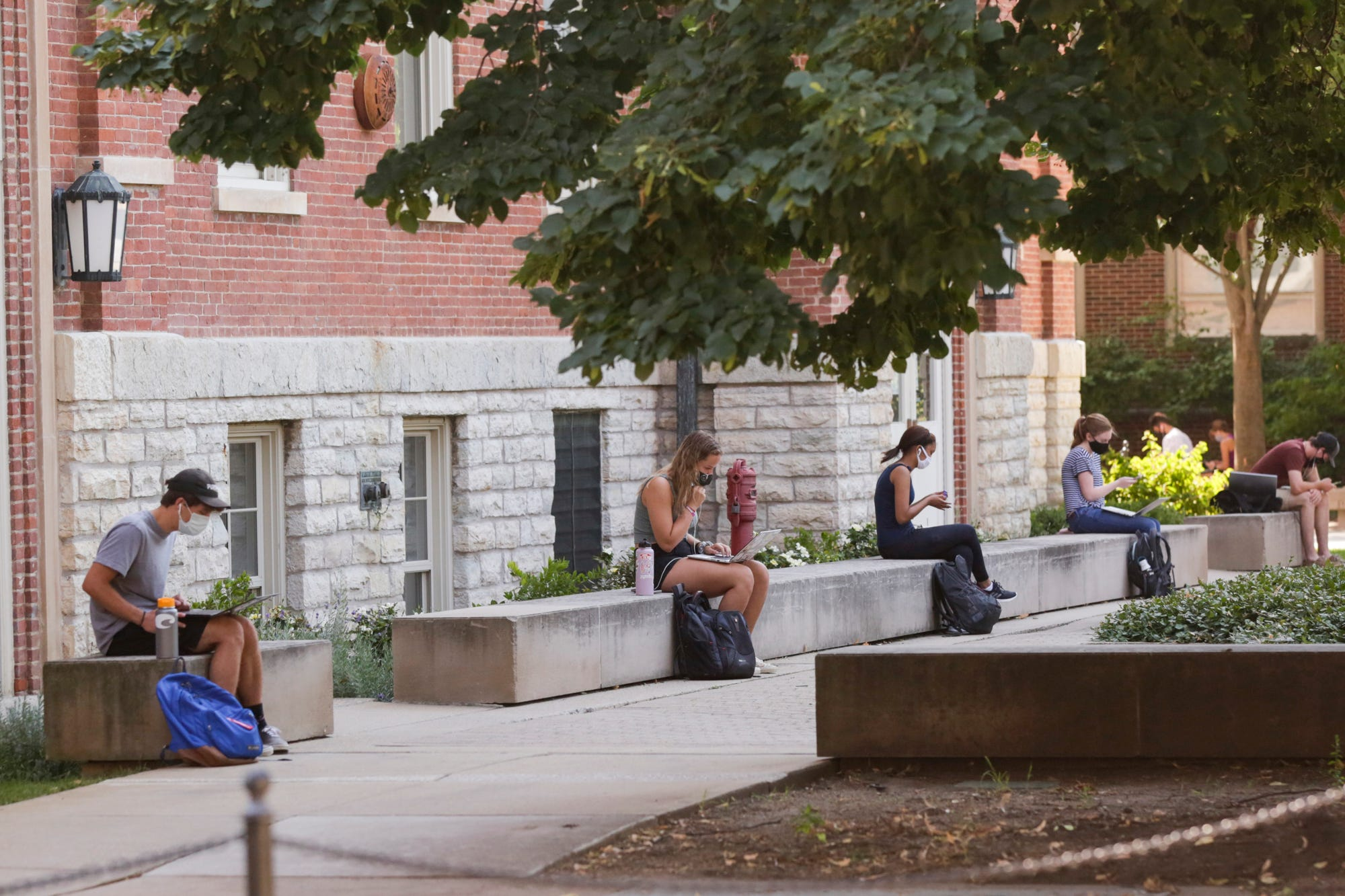 Students sit spaced out by Purdue's University Hall on Aug. 24 in West Lafayette, Indiana.