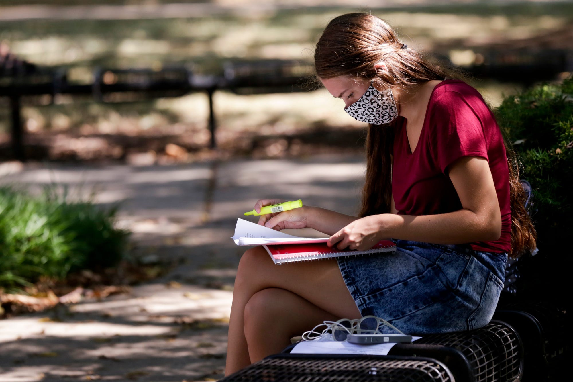 Sarah Connors, a senior animal science major at Purdue University, sits in the shade by the Purdue Bell tower before her afternoon classes Monday in West Lafayette.