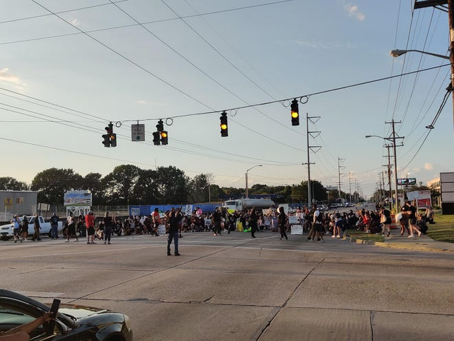 Law enforcement officers in riot gear meet with protesters who were marching in the road on Amabassador Caffery Parkway in Lafayette, LA, on Aug. 23, 2020.