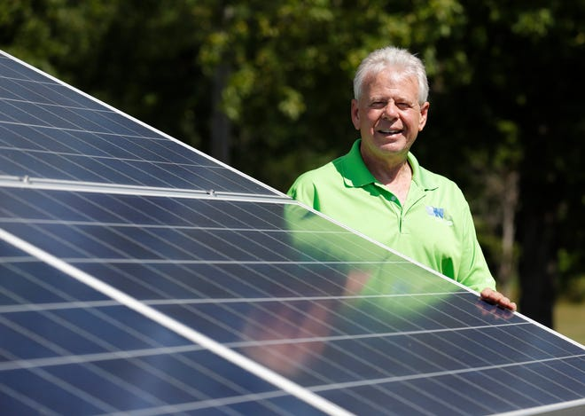 Dick Peffley, general manager of the Lansing Board of Water & Light, stands near his backyard solar array, Friday, Aug. 21, 2020, in Delta Township.