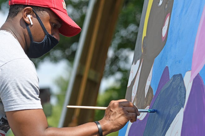Braxton Daniels III works on a mural outside Ovalwood Hall on Monday.