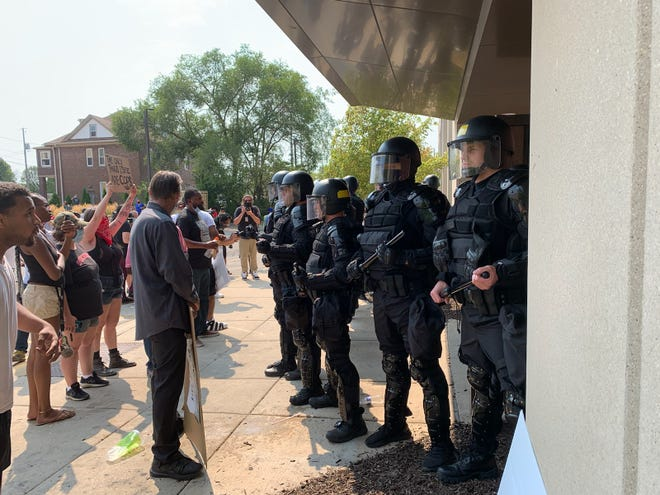 Police guard the entrance of the Kenosha Public Safety Building after crowds rushed the door trying to attend a planned news conference last August.