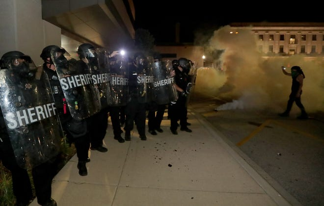 Protesters confront Kenosha County sheriff's deputies outside the Kenosha Police Department in Kenosha on Sunday, Aug. 23, 2020. Kenosha police shot a man Sunday evening, setting off unrest in the city.