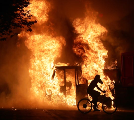 A man on a bike rides past a city truck on fire outside the Kenosha County Courthouse in Kenosha on Sunday, Aug. 23, 2020. Kenosha police shot a man earlier in the evening setting off unrest in the city.