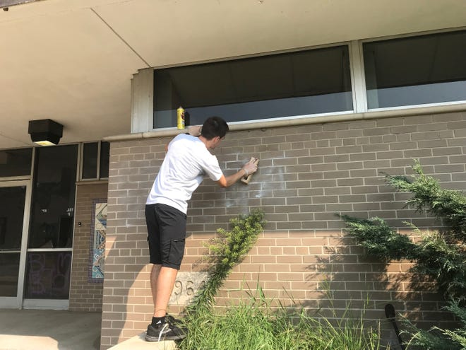 Troy Limbaugh of Kenosha scrubbed graffiti off the wall of the public library in downtown Kenosha on Monday morning.