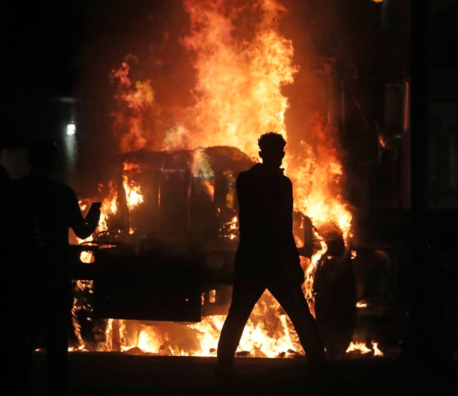 A man is seen as a city truck is on fire outside the Kenosha County Courthouse in Kenosha on Sunday, Aug. 23, 2020. Kenosha police shot a man that evening, setting off unrest in the city.