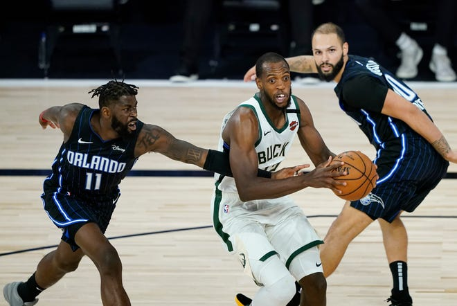 Bucks forward Khris Middleton drives past the Magic's James Ennis III during the second half.