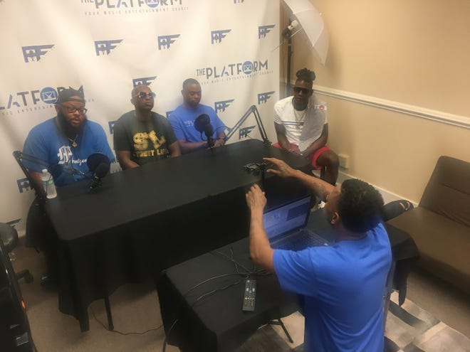 Noah Baker, right, of The Platform sets up a video podcast Saturday discussing gun violence. Seated are, from left, Comedian Blueski Blue, hip hop artist YunRo, and Lawn Boyz members Lil James and King South.