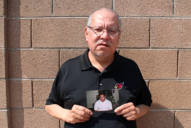 Auska Mitchell holds a photograph of his nephew, Lezmond Mitchell, on Aug. 21, 2020, in the Phoenix area. Lezmond Mitchell is scheduled to be executed Aug. 26, and the Navajo Nation is urging to spare his life on the basis of cultural beliefs and sovereignty.