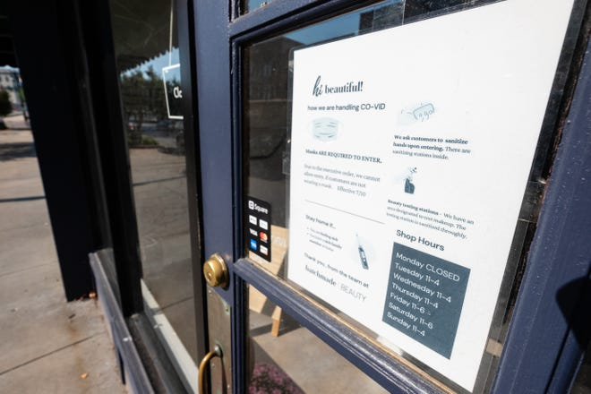 A sign telling customers about the measures being taken to prevent the spread of COVID-19 is posted on the door of batchmade BEAUTY in downtown Port Huron. The sign asks customers to wear a mask, sanitize their hands upon entering and to stay home if they're feeling sick.