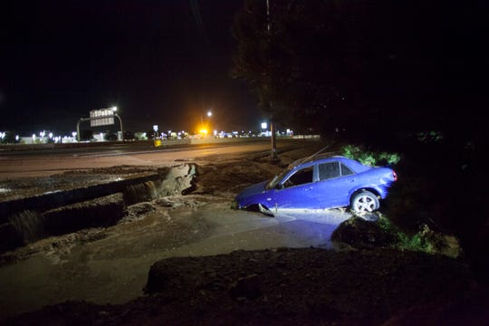 A car comes to rest between I-15 and the Dixie Convention Center after flood water moved barricades and washed away the shoulder Monday, Aug. 24, 2020.