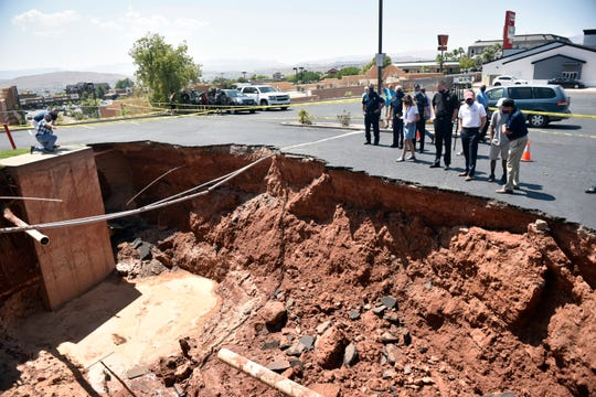 Gov. Gary Herbert and St. George Mayor Jon Pike in front of a sinkhole that opened in the parking lot of the Ramada by Wyndham hotel during a monsoon on Aug. 23, 2020.
