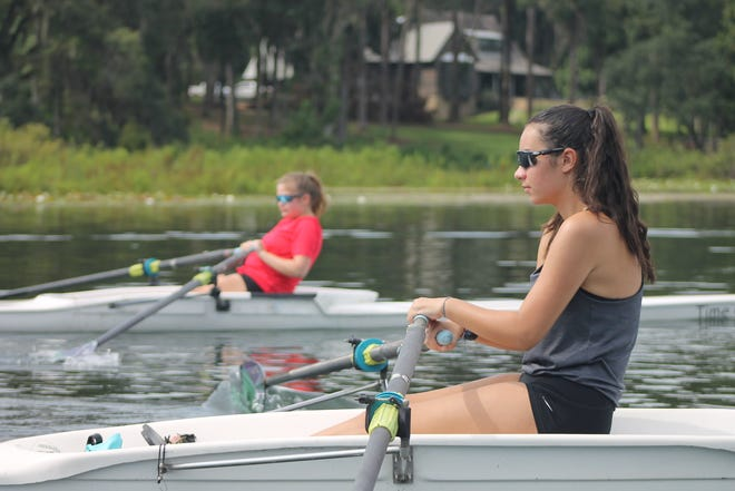 Chiles classmates Karys Whitaker (red shirt) and Sophia Birriel practice in their boats at Lake Hall.