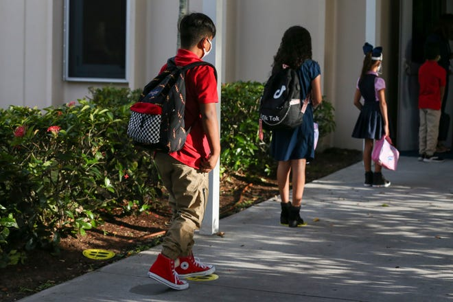 """The St. Lucie County Sheriff's Office, teachers, school district officials and community members welcome students on the first day of school with signs, smiles and support at Lakewood Park Elementary on Monday, Aug. 24, 2020, in St. Lucie County. The effort was a modified version of the school's annual Tunnel of Hope event. """"It's different because normally they're inside in the hallways and this year, for safety and social distancing, it is outside,"""" said Lydia Martin, the St. Lucie County schools chief communications director. """"We want the kids to feel the excitement and that we're happy to have them back, just like we do every year."""""""