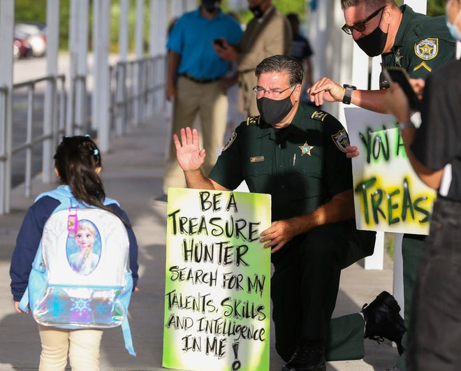 St. Lucie County Sheriff Ken Mascara (middle) and deputy Todd Hogan (right) welcome a student on the first day of school at Lakewood Park Elementary School on Monday, Aug. 24, 2020, in St. Lucie County.