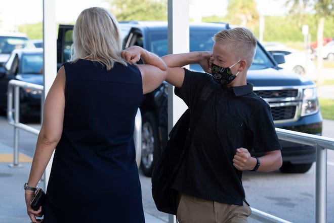 """Storm Grove Middle School Principal Anne Bieber (left) elbow bumps with 7th grade student Jackson Summerall at the start of the first day of school Monday, Aug. 24, 2020, in Indian River County. Students are returning to in-person classes for the first time since March, when COVID-19 unexpectedly shut down schools across the Treasure Coast. """"We are just happy to have our kids back,"""" Bieber said. """"Our teachers are ready, we are excited."""""""