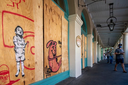 A few tourists walk past the boarded up French Market on the day Tropical Storm Marco was expected to hit the Gulf Coast.