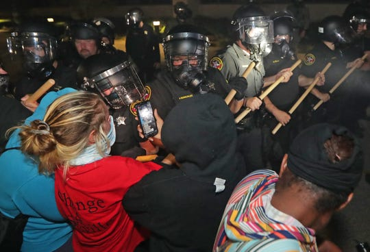 Police in riot gear confront protestors outside the Kenosha Police Department in Kenosha on Sunday, Aug. 23, 2020. Kenosha police shot a man Sunday evening, setting off unrest in the city after a video appeared to show the officer firing several shots at close range into the man's back