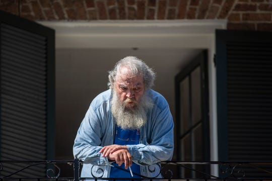 Cliff Ocheltree leans on the railing of his balcony in the French Quarter on the day Tropical Storm Marco was expected to hit the Gulf Coast. He and his wife were in the city during Hurricane Katrina and are now much more prepared for extreme weather events.