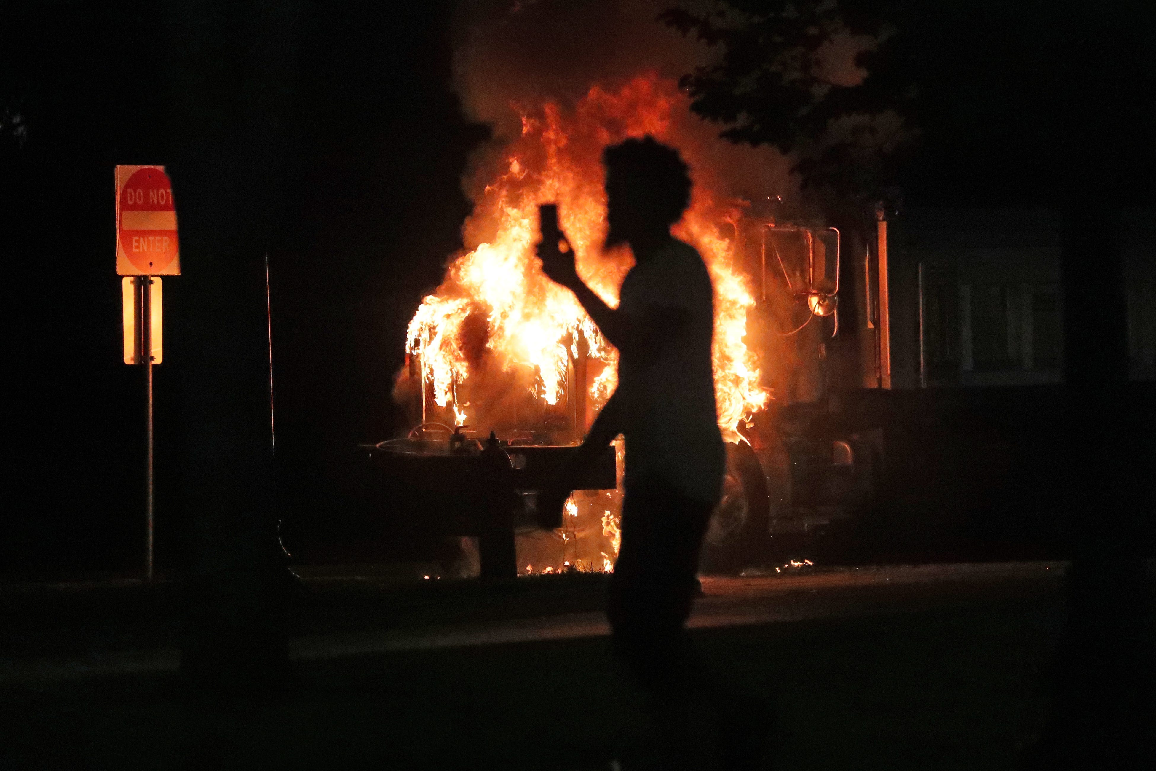 A man records a city truck on fire outside the Kenosha County Courthouse in Kenosha on Sunday, Aug. 23, 2020. Kenosha police shot a man Sunday evening, setting off unrest in the city. Protests broke out after police shot Jacob Blake, 29, a Black man.