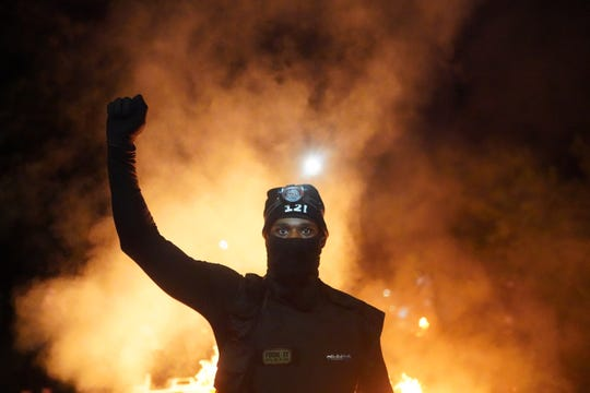 A protester holds his fist in the air during a protest against racial injustice and police brutality early in the morning on August 23, 2020 in Portland, Oregon.