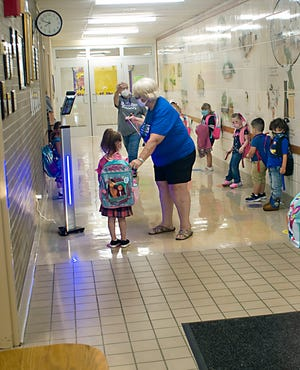 Children stand in line as they wait to have their temperature taken using an infared scanner on Monday's first day of class at B.L. Miller Elementary School in Sebring.