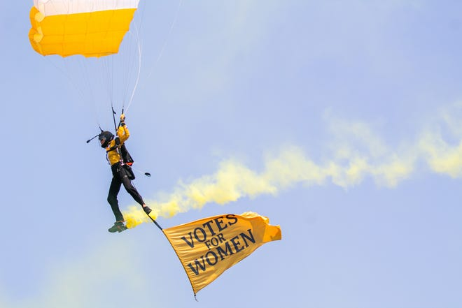 """Karen """"Lew"""" Dalton of the Highlight Pro Skydiving Team flies a flag beneath her parachute to commemorate the suffragists who fought for women's right to vote in the early 20th century. Dalton and three other members of her team participated in the ceremonial jump at Valley Forge National Historical Park in King of Prussia, Pa., on Tuesday."""