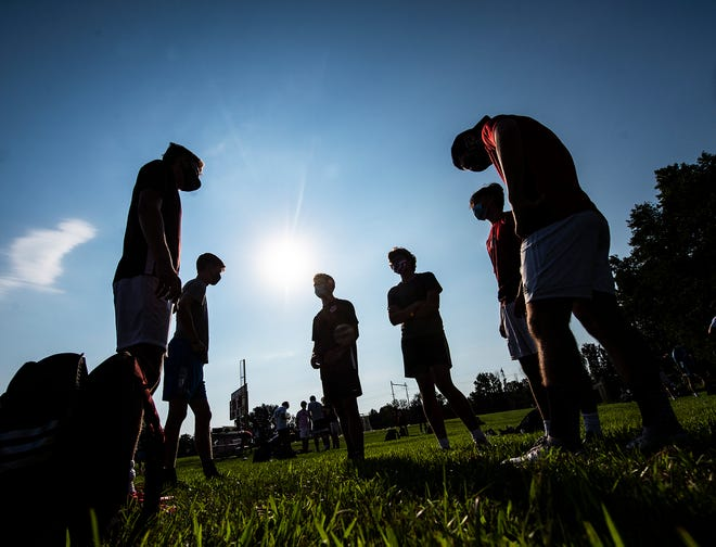 Silhouette of varsity and junior varsity players, wearing their masks, catch up on things before the start of boys soccer practice at Holy Ghost Prep in Bensalem on Tuesday.