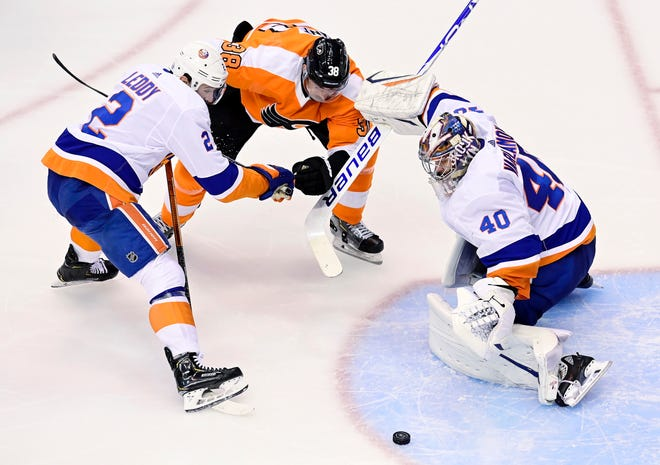 Islanders goaltender Semyon Varlamov makes a save as teammate Nick Leddy and Flyers center Derek Grant look for the rebound during Game 1.