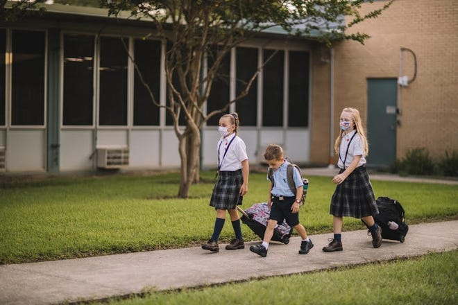 Local Catholic school students walk to class.