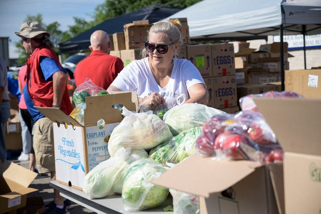 A volunteer fills bags with a variety of groceries for families at the FAITH Neighborhood Center food drop in Groveland on Friday, April 3, 2020. [Cindy Peterson/Correspondent]