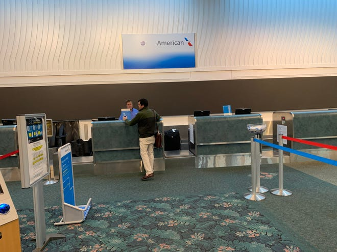A departing air traveler checks his suitcase in at the ticket counter for American Airlines at Daytona Beach International Airport earlier this year. DBIA announced that American Airlines will add flights to Philadelphia and Dallas/Fort Worth beginning Dec. 15.