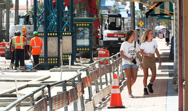 A couple of Beach Street shoppers walk along the sidewalk Tuesday, protected by the safety barriers separating the street construction from the open businesses and their patrons.