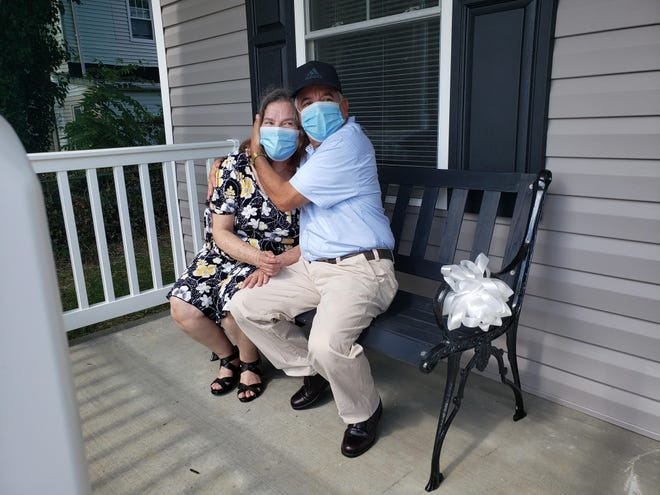 Rosa Castillo and Ramon Peralta sit on the front porch of their first home on New Street Aug. 7