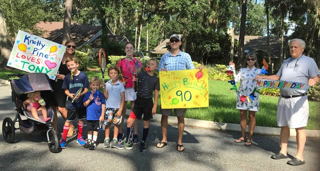 Neighbors of Vicki and Tony Trabert gathered with signs to celebrate Tony's 90th birthday.