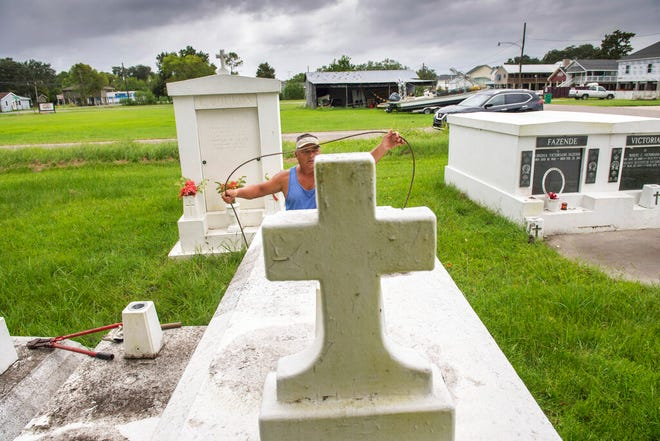 Jerry Parria uses steel cable and metal anchors to tie down four tombs belonging to his grandparents and uncles in a small cemetery near Lafitte, La., as residents along the Louisiana coast prepare for two tropical storms, Monday. Parria said the tombs floated away during a previous hurricane.