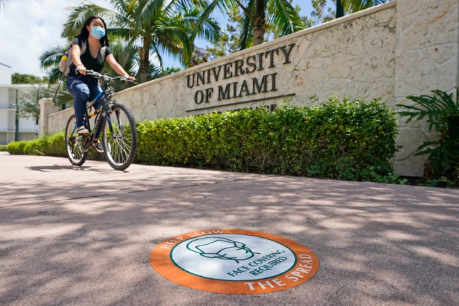 A cyclist, wearing a mask to prevent the spread of the new coronavirus, rides by an entrance to the University of Miami on Tuesday in Coral Gables.