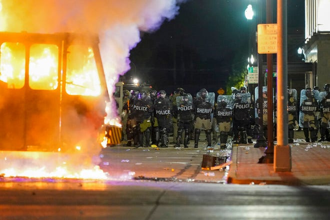Police stand near a garbage truck ablaze during protests, Monday in Kenosha, Wis., sparked by the shooting of Jacob Blake by a Kenosha police officer a day earlier.