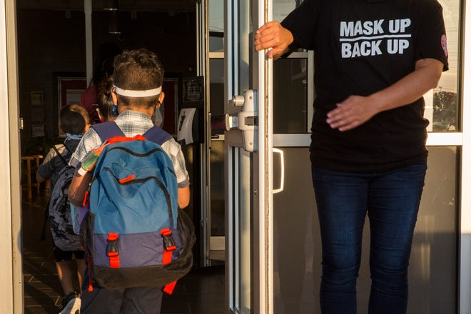 A staff member holds the door open for kids on the first day of school at Goodwin Frazier Elementary School in New Braunfels, Texas, on Tuesday. The number of Americans newly diagnosed with the coronavirus is falling — a development experts credit at least partly to increased wearing of masks — even as the outbreak continues to claim nearly 1,000 lives in the U.S. each day.