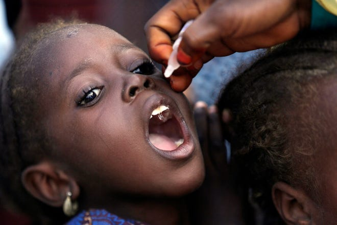 A health official administers a polio vaccine to a child in August 2016 at a camp for people displaced by Islamist Extremists, in Maiduguri, Nigeria. Health authorities on Tuesday declared the African continent free of the wild poliovirus after decades of effort, though cases of vaccine-derived polio are still sparking outbreaks of the paralyzing disease in more than a dozen countries.